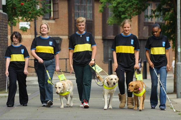 Members of UK's first blind cricket team preparing to carry the Para Olympic torch with with their guide dogs.  Photo:PA