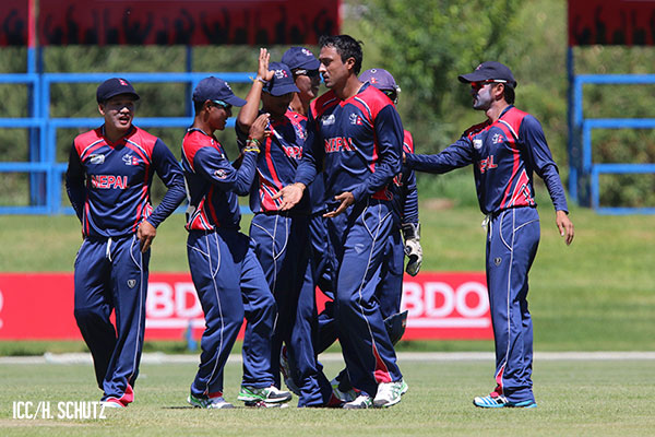 Nepal players celebrate after a wicket by Paras Khadka (centre). Photo: ICC/Helge Schutz